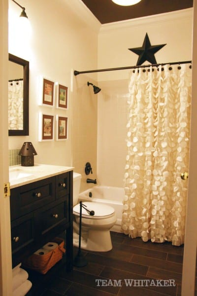 This guest bathroom features neutral colors, a textured shower curtain and some unexpected pops of fancy, including a painted ceiling and faux wood floor tiles.